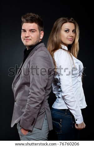 Image of a young happy couple, side view, dark background