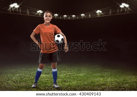 Image of asian woman holding soccer ball on the soccer field