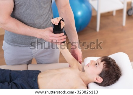 Image of boy lying on physiotherapy plinth doing exercises