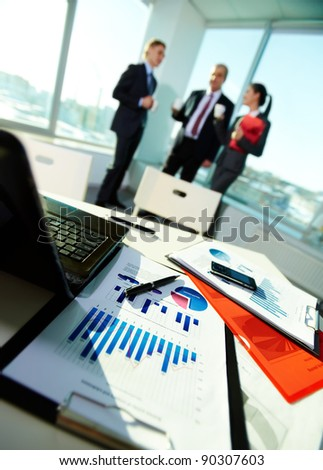 Image of business documents on workplace with three partners on background