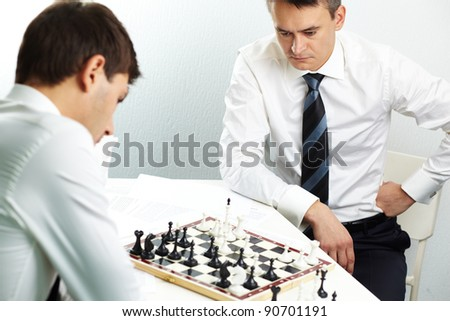 Image of businessman thinking of strategy while playing chess