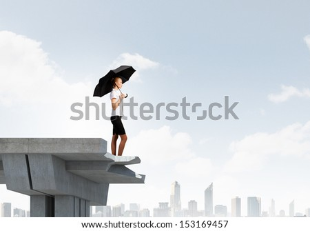 Image of businesswoman standing at the edge of bridge. Risk concept