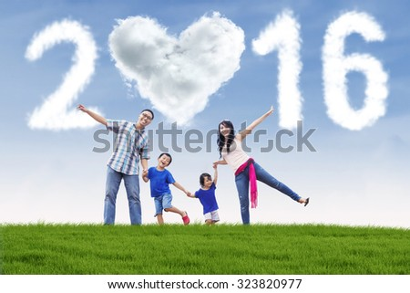 Image of cheerful asian family holding hands on the meadow with cloud shaped numbers 2016 and heart symbol