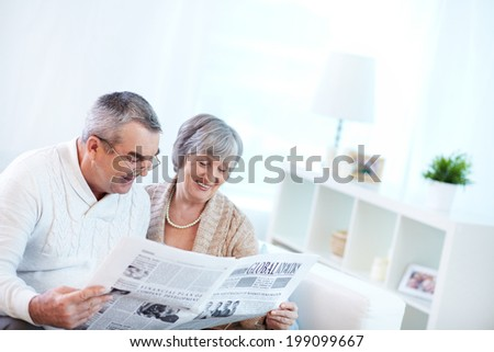 Image of couple of pensioners reading newspaper at home