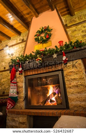 Image of fire burning in a fireplace decorated in Christmas style