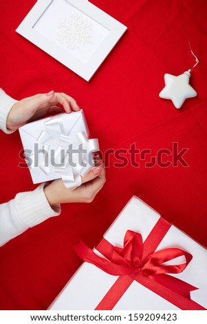 Image of giftbox held by female surrounded by other xmas presents on red background
