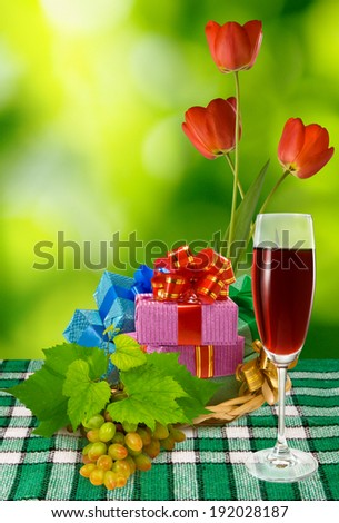 ... with wine, many gifts and flowers on a green background - stock photo