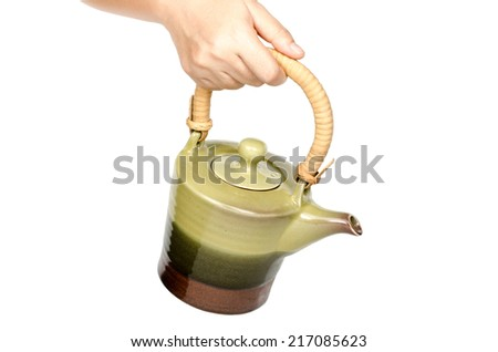 Image of hand holding Chinese ceramic tea pot isolate on white background