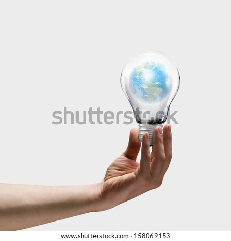 Image of human hand holding bulb with earth planet inside. Elements of this image are furnished by NASA