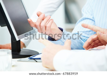 Image of human hands pointing at computer monitor during presentation