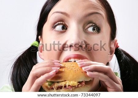 Image of hungry girl eating hamburger and looking aside