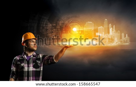 Image of man builder touching icon of media screen