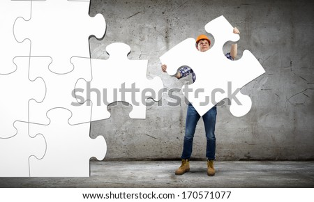 Image of man engineer connecting puzzle elements. Construction concept