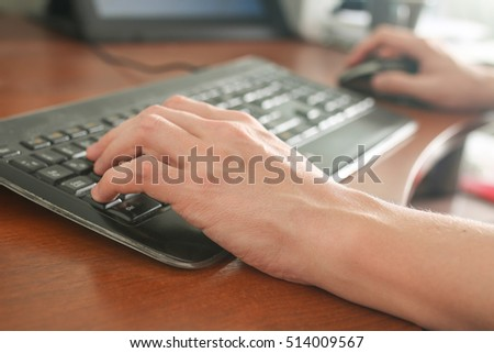 Image of man's hands typing on on keyboard . Selective focus