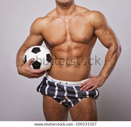 IMage of muscle man posing with ball