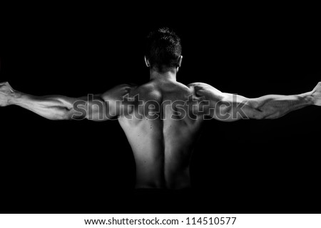 Image of muscular man posing in studio black and white
