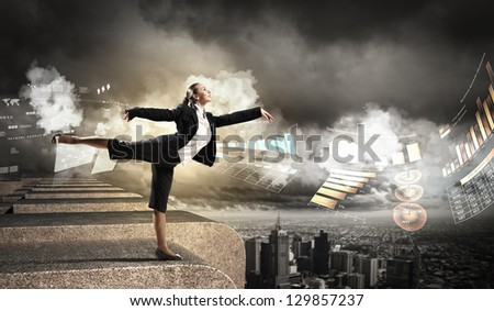 Image of pretty businesswoman balancing on the roof above cityscape