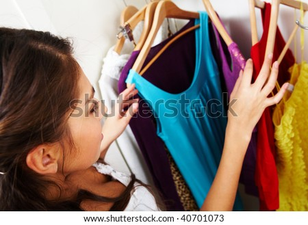 Image of pretty female looking through her wardrobe and choosing smart dress