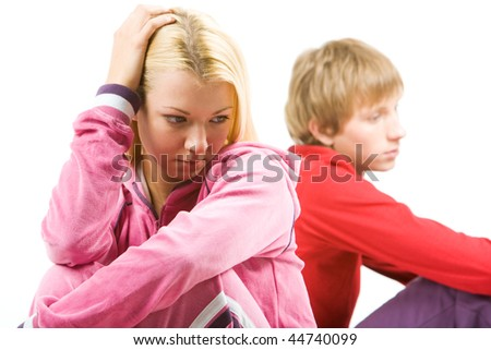 Image of sad girl with troubled guy at background after having an argument