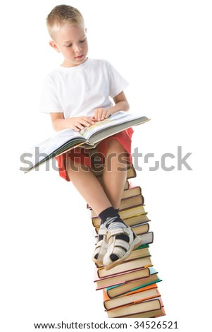 Image of schoolboy sitting on the heap of books and reading one of them