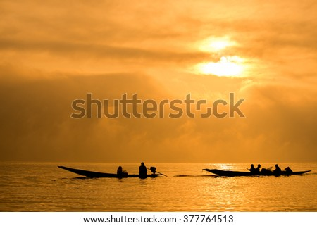 Image of silhouette, Myanmar transportation by engine boat at sunrise in Inle