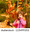 Image of small cute female child enjoying autumn nature, little pretty girl playing game in fall park, beautiful golden trees foliage, nice warm sunny day, carefree childhood - stock photo