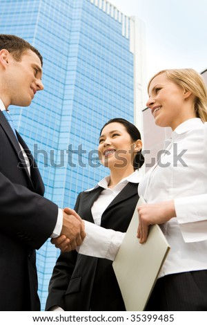 Image of successful partners handshaking after signing an agreement