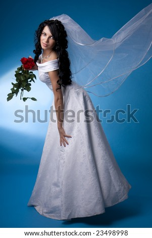 Image of the brunette bride with red roses on a blue background