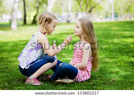 Image of two little cute girl playing on grass in park