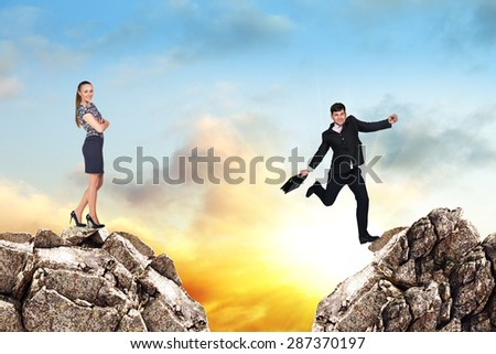 Image of young businessman jumping over gap at the sunset