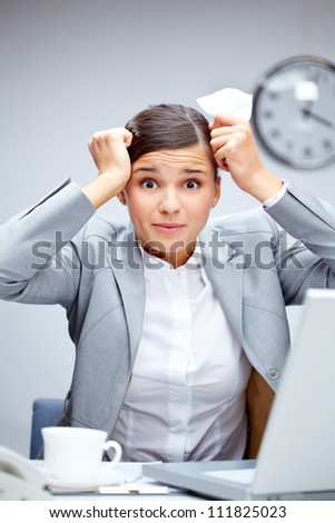 Image of young employer touching her head in confusion at workplace