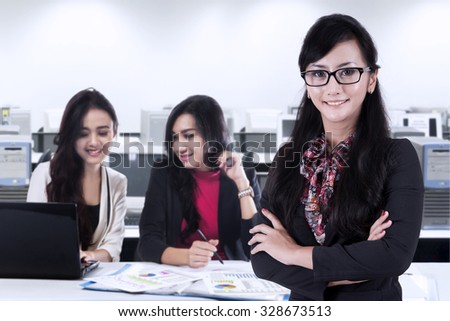 Image of young female manager standing in the office with two partners working on the back