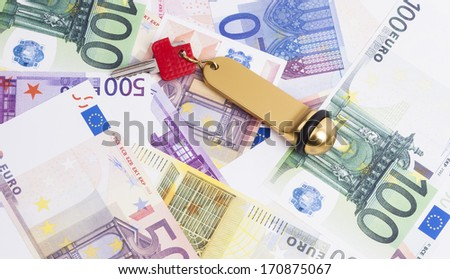Image shows heaps of banknotes and a key