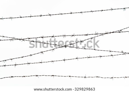 imprisonment, restriction concept - barb wire fence over gray sky