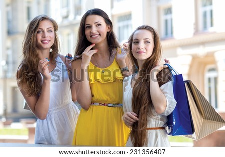 In front of the shop window. Three young and pretty girls are standing in front of shop window while going shopping
