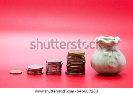 Increasing coins columns and small pot with US Dollar sign, isolated on red background.