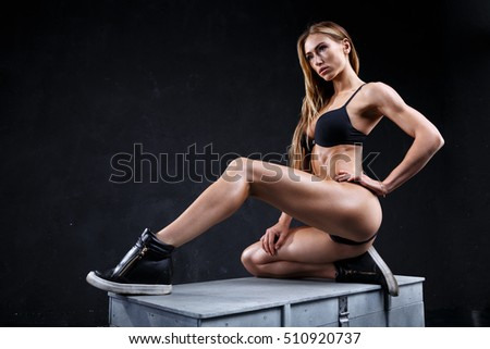 Incredible fitness model on the dark background