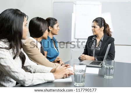 Indian business woman talking with her team during a meeting.