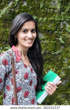 Indian woman standing outdoors with books.