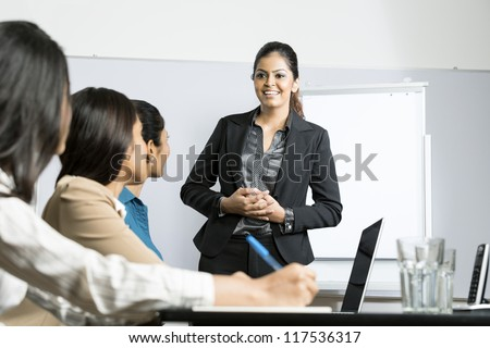 Indian woman standing up doing a presentation at a business meeting.