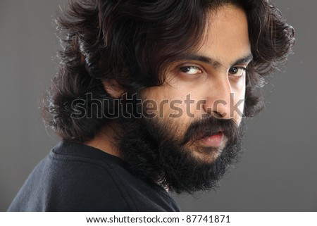 Indian young man with long hair on grey background.