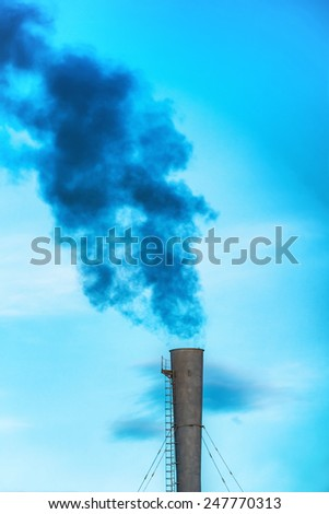 Industrial black toxic smoke from coal power plant on blue sky