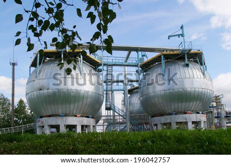 industrial oil pumps and cistern on a green summer meadow in a sunny day
