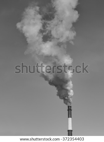 Industrial pipe with smoke on a sky background.