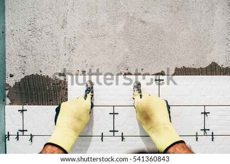 industrial worker, handyman installing small ceramic tiles on bathroom walls