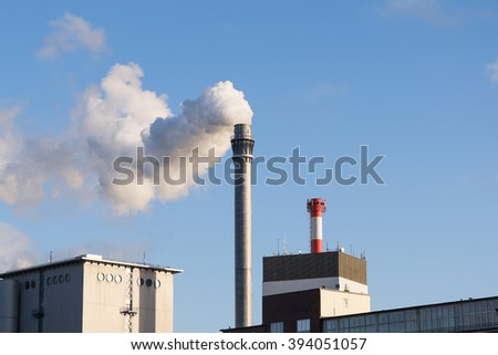 industry chimney with smoke and factory buildings against the blue sky with copy space