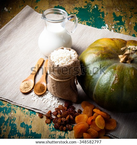 Ingredients for the rice porridge with dried fruits and spices in a pumpkin on a gray rustic napkin on the painted old wooden table. Toned.