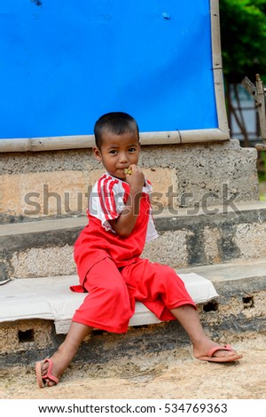 INLE LAKE, MYANMAR - AUG 30, 2016: Unidentified Burmese little boy in a red shirt. 68 per cent of Myanma people belong to Bamar ethnic group