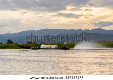INLE LAKE, MYANMAR - AUG 30, 2016: Unidentified Burmese man in bamboo boat with bags sails over the Inle Sap,a freshwater lake located in the Nyaungshwe Township of Taunggyi District of Shan State