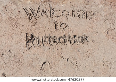 "Inscription ""Welcome to Paradise"" on a sand."